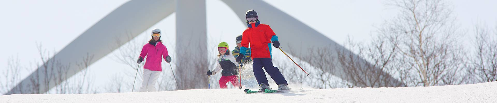 Family Skiing in front of turbine